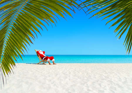 Christmas Santa Claus ontspannen op ligstoel bij oceaan zandige tropisch strand onder palmbladeren. Gelukkig reisbestemmingen Nieuwjaar aan hot begrip landen