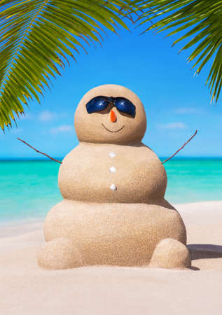 Sandy snowman in black sunglasses and carrot nose at tropical ocean beach under palm leaves. Happy New Year and Merry Christmas travel destinations concept Stock Photo