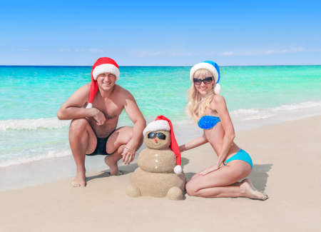 young friends: Young cheerful couple and funny sandy snowman sculpture in santa hats at sea beach. Happy New Year and Merry Christmas holidays vacation and hot travel tours concept