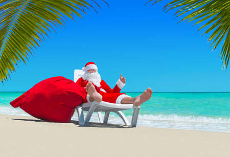 Santa Claus with big red merry Christmas sack thumbs up gesture by hand, relax on deckchair at ocean tropical beach under palm leaves. Happy New Year travel destinations concept.