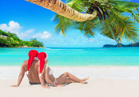 Romantic couple in red Christmas Santa hats hugging and tanning at island tropical palm sandy beach, Seychelles, Indian Ocean. Happy New Year holidays travel destinations concept.