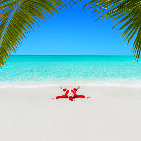 Santa Claus relaxing sunbathe at idyllic tropical ocean hot beach sand in turquoise water waves under the palm tree leaves. Merry Christmas and happy New Year travel background concept.