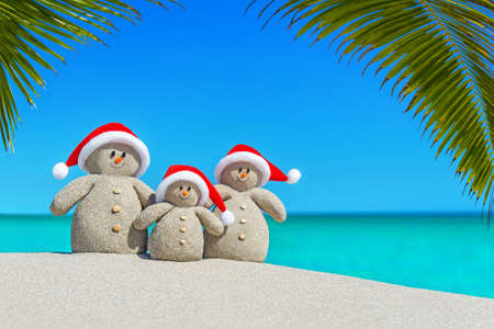 積極的沙子雪人家庭在紅色聖誕老人帽子在陽光海洋熱帶棕櫚灘。新年快樂和聖誕快樂概念熱旅遊目的地自然背景。 版權商用圖片