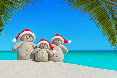 Pozitivní písečné rodiny sněhuláci v červených Santa klobouky na slunné oceánu tropické palmové pláže. Šťastný nový rok a Veselé Vánoce koncept pro teplé destinace cestovního ruchu přirozené pozadí. Reklamní fotografie