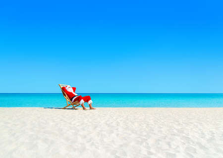 Santa Claus tan relaxing on sunlounger at sandy tropical ocean beach. Happy New Year and Merry Christmas travel destinations to hot countries concept