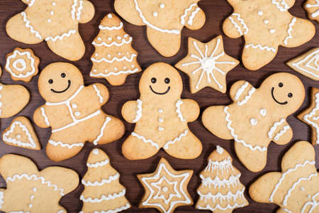 Christmas homemade gingerbread men, fir trees, stars and hearts cookies over wooden background