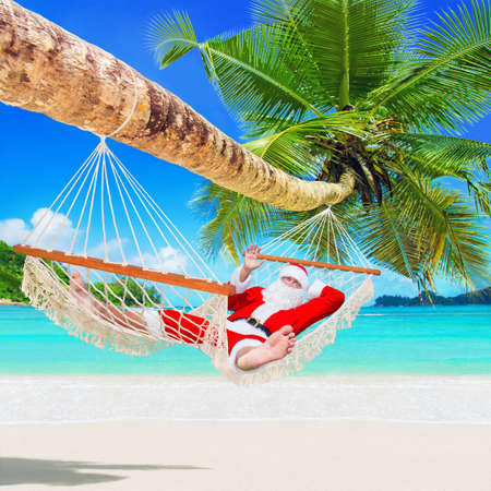 Santa Claus sunbathe in white cozy mesh hammock in shade of coconut palm tree at sandy ocean island beach. Happy New Year and Merry Christmas travel destinations for tropical vacations concept 스톡 콘텐츠