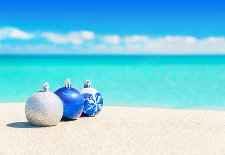 Christmas tree balls decorations on the sand of tropical ocean beach - happy New Year and Merry Christmas holidays travel destinations in hot countries concept 스톡 콘텐츠