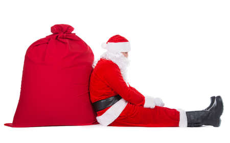Tired Santa Claus have rest sitting near big Christmas sack full of presents, gifts and surprises isolated on white background, New Year or xmas holiday concept