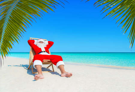 Santa Claus relax on wooden beach chair at ocean tropical palm beach seaside. Happy New Year and Merry Christmas travel destinations for tropical vacations concept Stock Photo