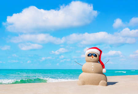 Positive sandy snowman in red Santa Claus hat and sunglasses at cloudy sunny ocean beach. Happy New Year and Merry Christmas travel destinations concept for tropical vacations.