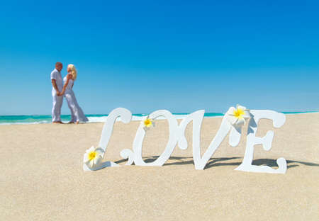 Loving couple at tropical ocean sandy beach with love word decoration and frangipani flowers. Proposal, wedding, valentines day or honeymoon background concept. Blonde woman in long dress and her man 스톡 콘텐츠