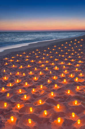 Sunset ocean sandy beach decorated with lot flare lights of candles. Marvellous romantic sea vacation seascape or honeymoon vertical background concept. 스톡 콘텐츠