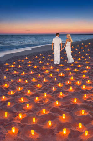 Loving couple in white cloth at tropical sunset ocean sandy beach decorated with lot of candles lights. Marvellous romantic seascape, proposal, wedding, valentines day or honeymoon vertical background