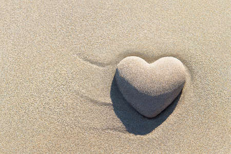 Heart made of sand with shadow on sandy beach background, Saint Valentines day greeting cards, romantic, love, honeymoon, proposal or wedding concept.