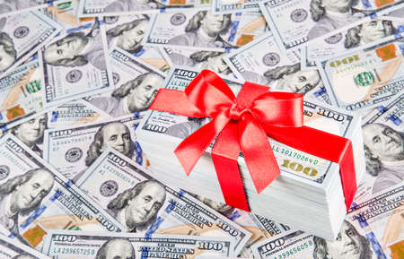 Gift  with big red bow ribbon made of united states dollars currency bundle on many new one hundred USA money banknotes background. Financial successful business profits concept.