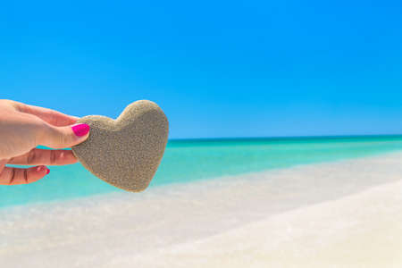 Heart made of sand in womans hand against tropical ocean beach background. Romantic, love, honeymoon, wedding or Saint Valentines day greeting cards concept.