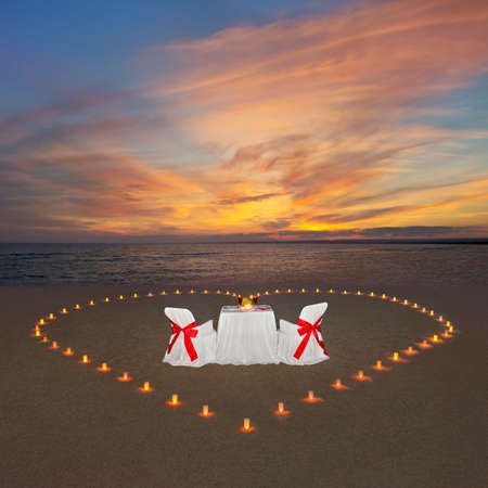 Romantic dinner with candles heart, luxury decorated table and wine at ocean tropical sandy beach during marvellous sunset. Proposal, wedding or honeymoon background concept. 스톡 콘텐츠