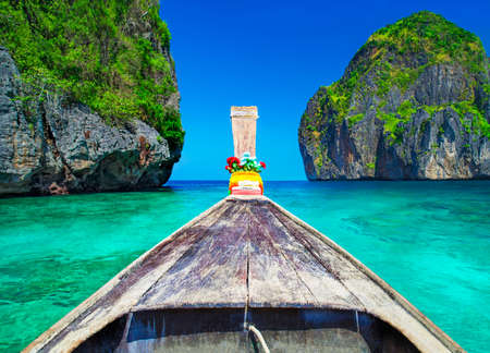 Traditional wooden longtail taxi boat nose with decoration flowers and ribbons at Maya Bay beach against steep limestone hills. Main Thailand tourist attraction background, Ko Phi Phi Leh Island