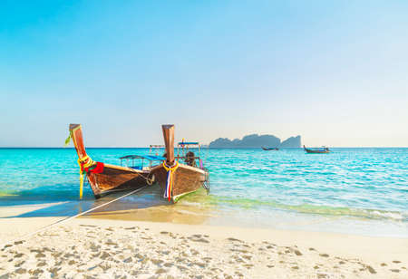 Two traditional thai longtail wooden boats at famous sunset Long Beach, Thailand, Koh Phi Phi Don island, Krabi province, Andaman sea 스톡 콘텐츠