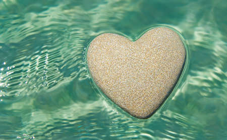 Heart made of sand floating in transparent turquoise ocean ripples water background, Saint Valentines day greeting cards, romantic love, honeymoon, proposal or wedding concept.