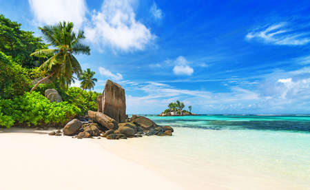 Seychelles, tropical beach Anse Royale, most popular beach on island Mahe. Paradise background with  impressive nature, white sand, clear water, coconut palms, granite rocks and coral reef protection