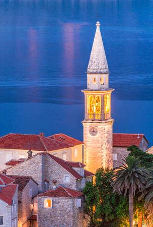 Campanile della Chiesa di San Giovanni Battista with tower clock in Budva old medieval walled city against Adriatic Sea in night, Montenegro, Europe. Vertical travel background. 스톡 콘텐츠