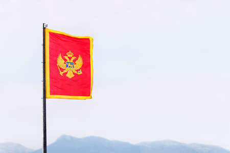The flag of Montenegro (red, with the two-headed eagle coat of arms in the middle, and golden borders) officially adopted on 13 July 2004 in the statehood day.