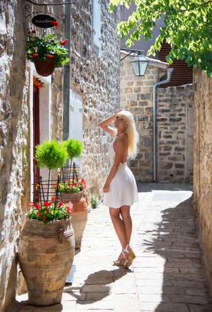 Cute Blonde tourist woman in white dress walking home along the small fairy-tale street with flowers in Old Budva city in sunny summer day. Montenegro travelling concept, Europe.