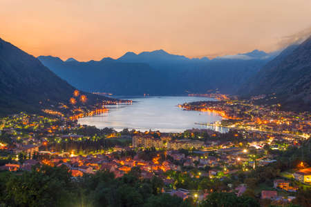 Sunset Bay of Kotor (Boka Kotorska) at Adriatic Sea, southwestern Montenegro. Night airview with firework from Dinaric Alps at towns of Kotor, Risan, Tivat, Perast, Prcanj and Herceg Novi 写真素材