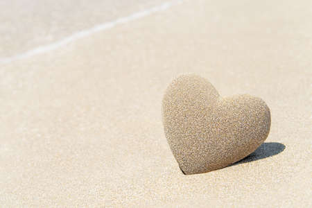 Heart made of sand with shadow on sandy beach background against sea wave foam, Saint Valentines day greeting cards, romantic, love, honeymoon, proposal or wedding concept.