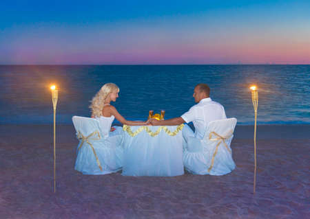 Loving couple in white cloth at romantic dinner with torch flares, candles and luxury decorated table against ocean tropical sandy marvellous sunset beach. Proposal, wedding or honeymoon concept