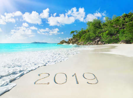 Perfect tropical palm sandy beach Anse Georgette at Praslin island, Seychelles - travel vacation season new year 2019 background, caption handwritten on sand, against waves, blue sky and forest Stock Photo