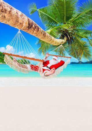 Santa Claus sunbathe in white cozy hammock in shadow of coconut palm tree at sandy ocean island beach.