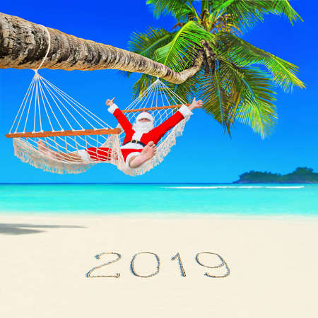 Santa Claus relax at sun in white cozy hammock thumbs up positive gesturing under coconut palm tree at tropical ocean beach