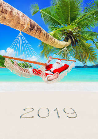 Santa Claus sunbathe in white cozy mesh hammock in shade of coconut palm tree 스톡 콘텐츠