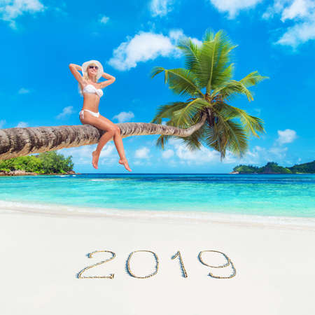 Cute blonde woman in white bikini and hat at palm tree against tropical ocean beach with inscription 2019 on white sand.