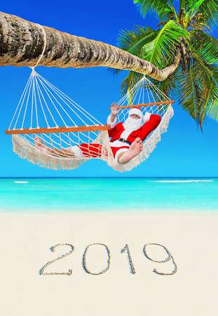 Santa Claus relax in mesh hammock under coconut palm tree at tropical paradise ocean beach 스톡 콘텐츠
