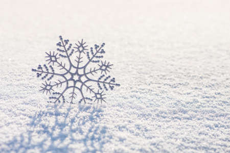 Winter horizontal background with shiny decorative silver snowflake on brilliant whiteness snow surface in sunset sunlight, Merry Christmas and Happy New year greeting cards concept
