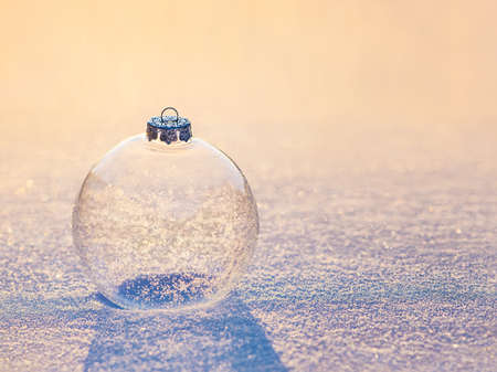 Christmas transparent glassy bauble ball with snowflakes shining in sunset light on snow brilliant surface. Happy New year greeting cards concept 스톡 콘텐츠