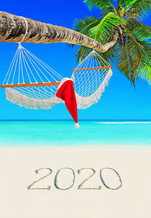 Handwritten happy new year 2020 caption on sand. Red Christmas Santa Claus hat on wooden mesh hammock under coconut palm tree at paradise tropical beach, Mahe island, Seychelles, Indian Ocean. 스톡 콘텐츠