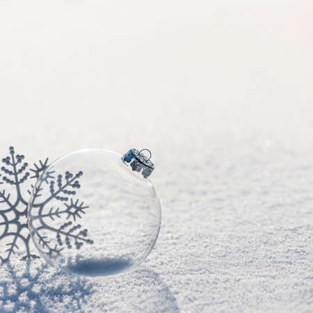 Winter background with transparent glass ball and silver snowflakes shiny on whiteness snow surface. Merry Christmas and Happy New year greeting cards concept 스톡 콘텐츠