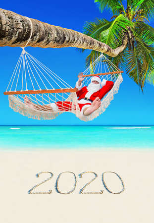 Santa Claus relax in mesh hammock under coconut palm tree at tropical paradise ocean beach with handwritten caption of happy New Year 2020 number on white sand, Christmas travel destinations concept. 스톡 콘텐츠