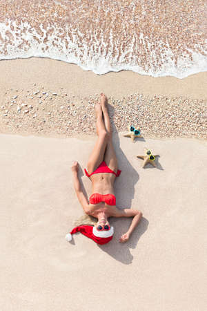 Pretty smiling blonde woman in Christmas red santa claus hat lying on tropical sandy ocean beach with sea stars in colorful yellow, blue and red heart shaped sunglasses. Holiday concept for New Years Day