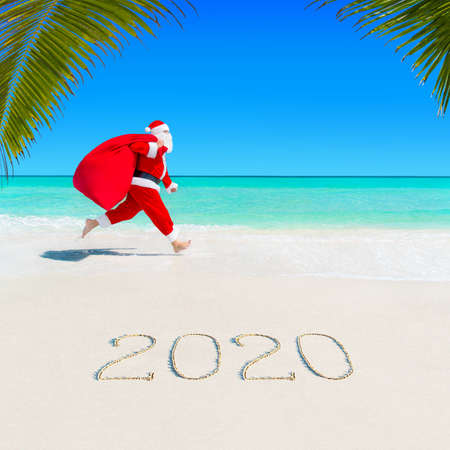 Christmas Santa Claus run jumping at ocean tropical sandy beach with large sack full of gifts - season 2020 New Year vacation and travel destinations concept