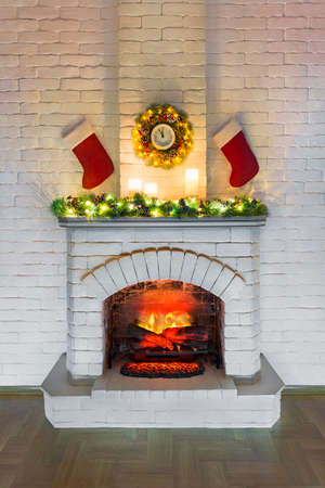 White fireplace with fire decorated for Christmas with candles, Santa Claus socks with gifts, new year fir tree branch and wreath with big clock on a white brick wall. Christmas concept, new year. 스톡 콘텐츠
