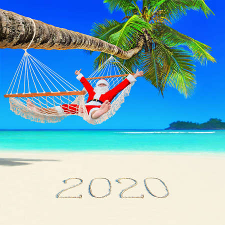 Santa Claus thumbs up hands positive gesturing relax in mesh hammock under coconut palm tree at paradise ocean beach with caption happy New Year 2020 on white sand,Christmas travel destination concept