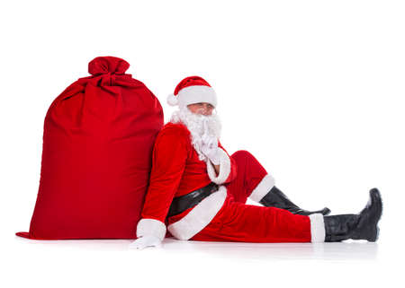 Santa Claus sitting near huge red Christmas sack full of gifts and surprises isolated on white background, New Year or xmas holiday concept