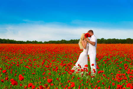 Loving couple with big flowers bouquet in white cloth kiss and hug in beautiful poppy field during romantic date. People in wild nature horizontal background with bright blue sky.