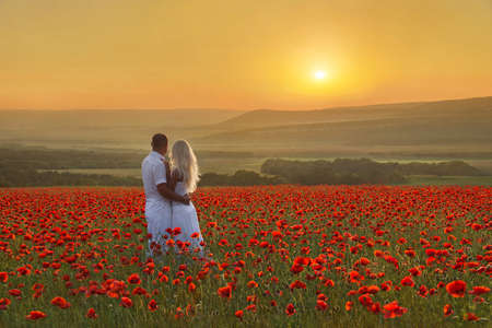 Loving couple hug one another during romantic date in marvellous spring poppy field with bright sunset above forest and mountains. People in wild nature landscape horizontal background.